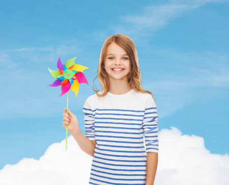 education, childhood and ecology concept - smiling child with colorful windmill toy photo