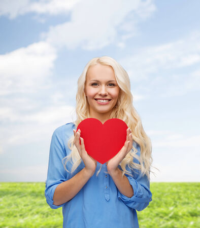 happiness, health and love concept - smiling woman with red heart photo