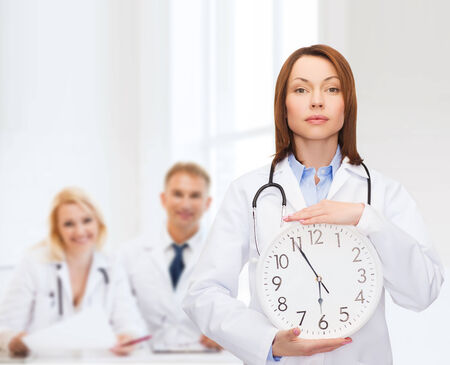 healthcare and medicine concept - calm female doctor with wall clock and stethoscope photo