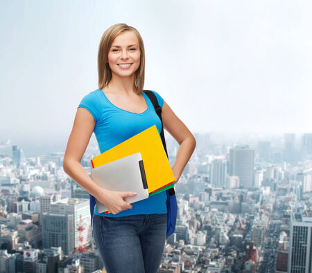 education, technology and people concept - smiling student with bag, folders and tablet pc computer standing photo