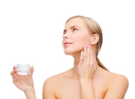 mimos: cosméticos, salud y el concepto de belleza - mujer hermosa que aplica la crema en su piel