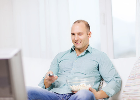 food, happiness and people concept - smiling man with popcorn watching movie at home photo