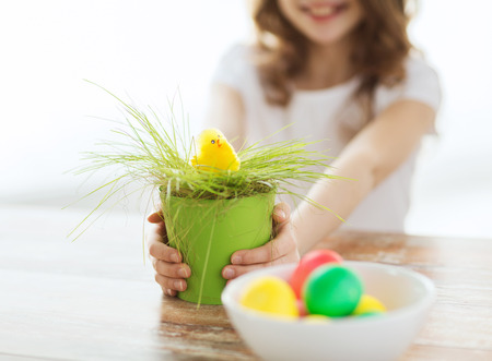 chiken: easter, holiday and child concept - close up of girl holding pot with green grass and yellow chiken toy with bowl of colored eggs