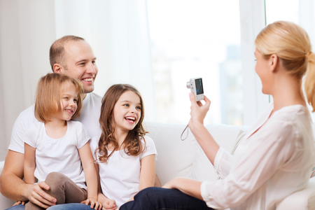 taking photograph: family, children, photography and home concept - smiling happy mother taking picture of father and two daughter at home Stock Photo