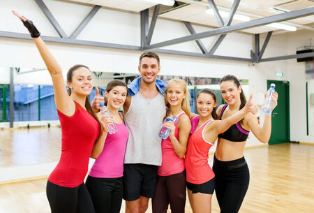 fitness, sport, training, gym and lifestyle concept - group of happy people with water bottles and towel in the gym waving hands photo
