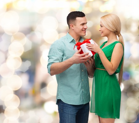 happiness, holidays, celebration and couple concept - smiling couple with gift box photo