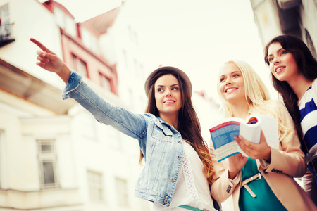 holidays and tourism concept - beautiful girls looking for direction in the city Stock Photo