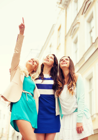 lost city: holidays and tourism concept - beautiful girls looking at something in the city