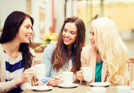 holidays and tourism concept - beautiful girls drinking coffee in cafe Stock Photo