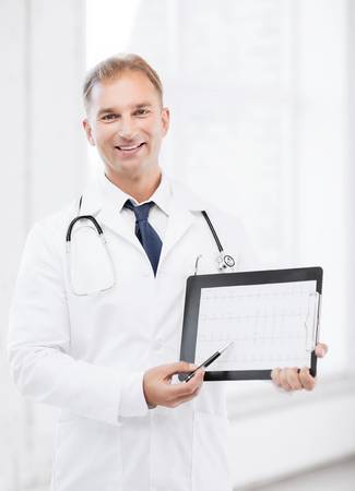 prescribing: healthcare and medical concept - male doctor with stethoscope showing cardiogram Stock Photo