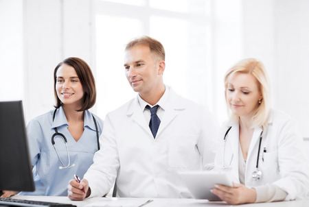 healthcare, medical and technology - group of doctors looking at computer on meeting photo