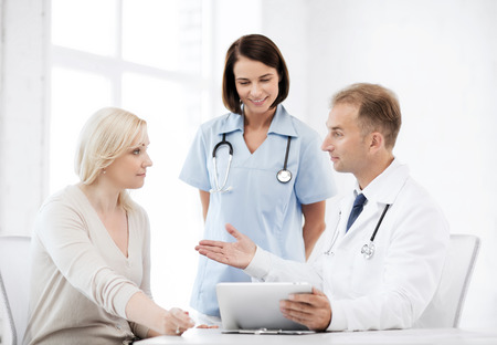 healthcare, medical and technology - doctor showing something to patient on tablet pc photo