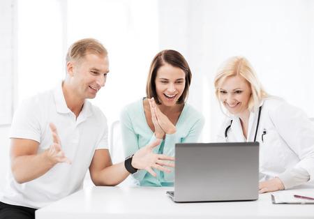 健康、医療、技術 - ラップトップを見て患者と医師