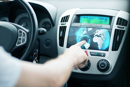 transportation and vehicle concept - man using car control panel photo