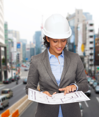 building, developing, consrtuction and architecture concept - smiling businesswoman in white helmet pointing finger to blueprint photo