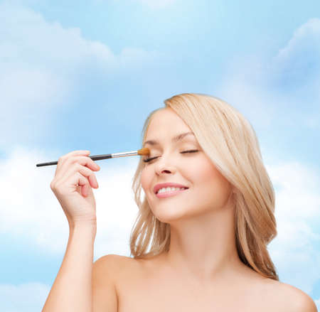 sensitive skin: cosmetics, health and beauty concept - beautiful woman with closed eyes and makeup brush Stock Photo