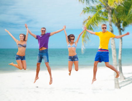 summer, holidays, vacation, happy people concept - group of friends or couples jumping on the beach photo
