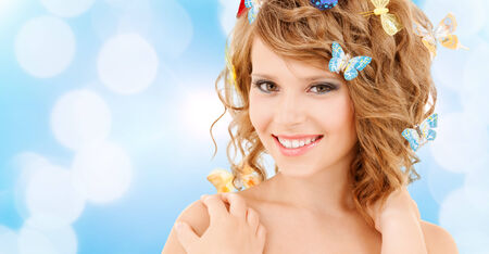 health and beauty concept - happy teenage girl with butterflies in hair photo