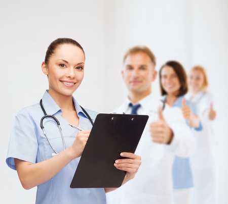 medical notes: healthcare and medicine concept - smiling female doctor or nurse with stethoscope and clipboard with team on the back showing thumbs up Stock Photo