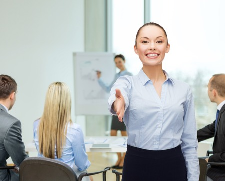 business, gesture and education concept - friendly young smiling businesswoman with opened hand ready for handshake photo