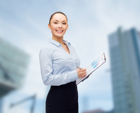 business and education concept - friendly young smiling businesswoman with clipboard and pen photo