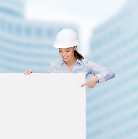 building contractor: building, developing, consrtuction and architecture concept - young smiling businesswoman in helmet pointing finger to white blank board Stock Photo
