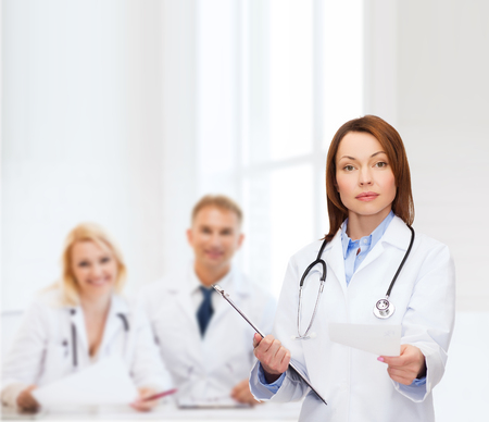 prescribing: healthcare and medicine concept - calm female doctor with clipboard and stethoscope