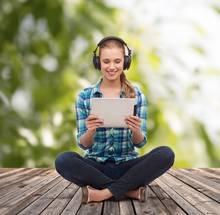 headphones: technology, internet and people concept - smiling young woman in casual clothes sitiing on floor with tablet pc computer and headphones