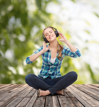 music and technology concept - smiling young woman sitting on floor and listeting to music with headphones photo