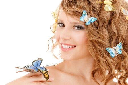 health and beauty concept - happy teenage girl with butterflies in hair and one sitting on her hand photo