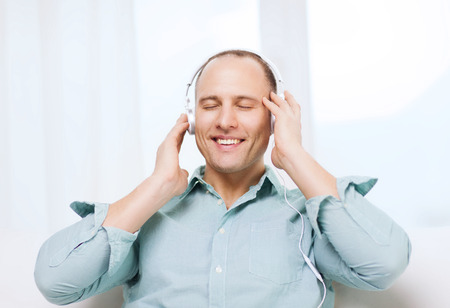 leisure and lifestyle concept - happy man with headphones listening to music at home photo