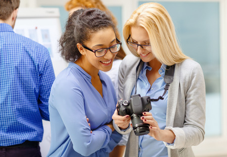 business, photography and startup concept - two smiling young women looking at digital camera at office photo