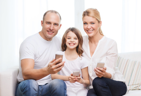 family, child, technology and home concept - smiling parents and little girl with smartphones at home photo