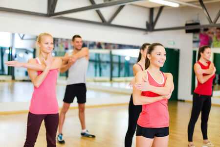 fitness, sport, training, gym and lifestyle concept - group of smiling people stretching in the gym Stock Photo