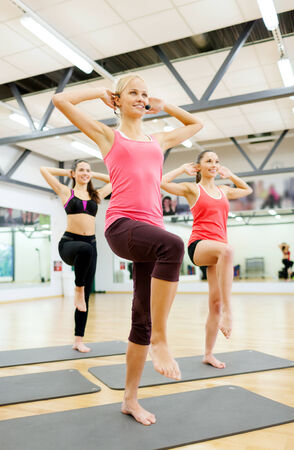 sportive: fitness, sport, training, gym and lifestyle concept - group of smiling female with trainer exercising in the gym