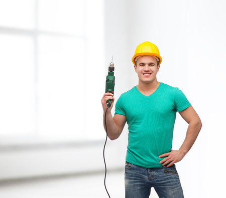 repair, construction and maintenance concept - smiling male manual worker in protective helmet with drill machine photo