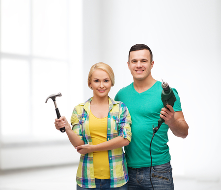 electric drill: repair, construction and maintenance concept - smiling couple with hammer and drill over white background
