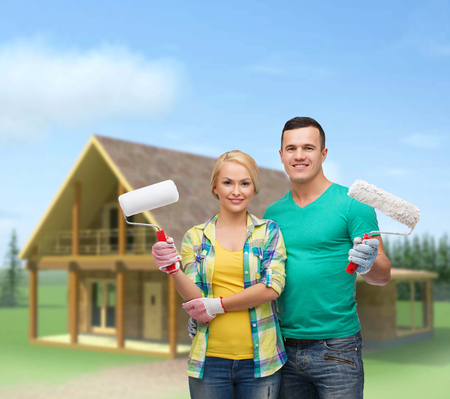 repair, construction and maintenance concept - smiling couple in gloves with paint rollers photo