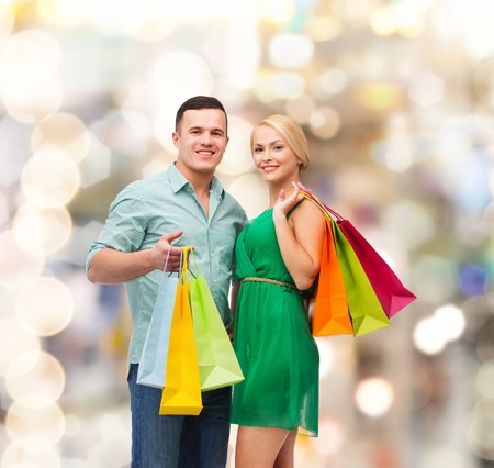 happiness, shopping and couple concept - smiling couple with shopping bags photo