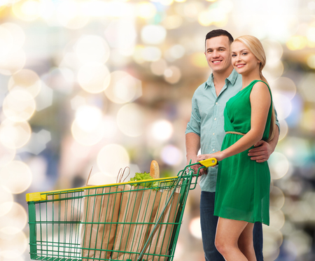 happiness, shopping and couple concept - smiling couple with shopping cart and food in it photo