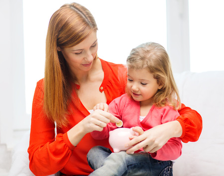 family, children, money, investmen and happy people concept - happy mother and daughter with small pink piggy bank photo
