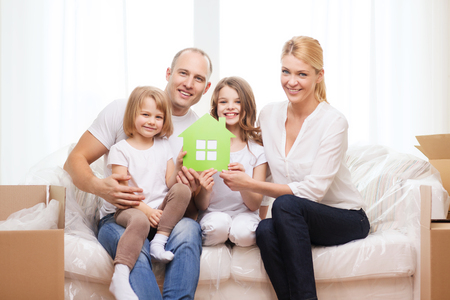 family, children, accomodation and home concept - smiling parents and two little girls holding green house photo
