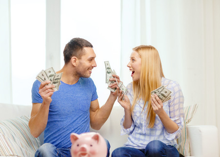 love, family, finance, money and happiness concpet - smiling couple with money and piggybank ot table at home
