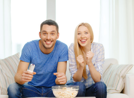 woman watching tv: food, love, family, sports, entretainment and happiness concept - smiling couple with popcorn cheering sports team at home