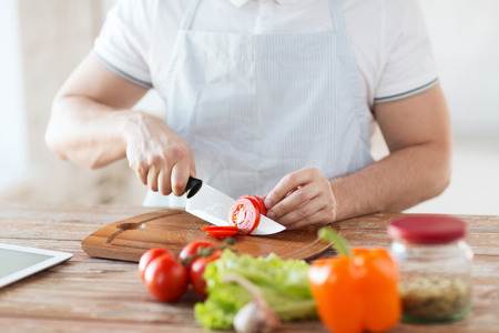 cooking and home concept - close up of male hand cutting tomato on cutting board with sharp knife photo