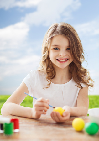 easter, holiday and child concept - smiling little girl coloring eggs for easter photo