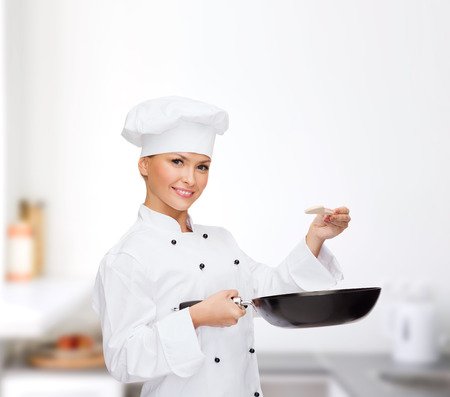 cooking and food concept - smiling female chef, cook or baker with pan and spoon tasting food photo