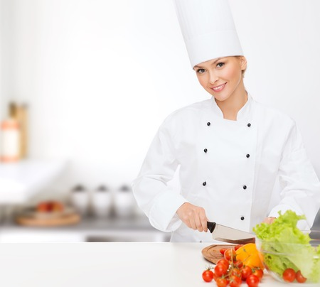 cooking and food concept - smiling female chef chopping vegetables photo