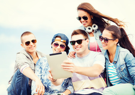 summer holidays, teenage and technology concept - group of teenagers taking picture with tablet pc photo