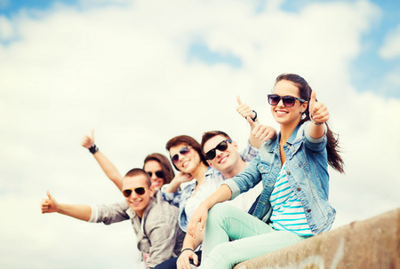 thumbs up: summer holidays and teenage concept - group of teenagers showing thumbs up